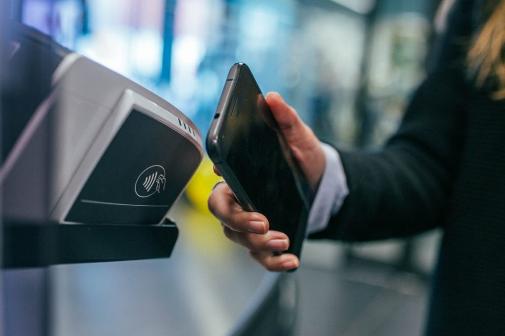 man swiping phone on payment terminal
